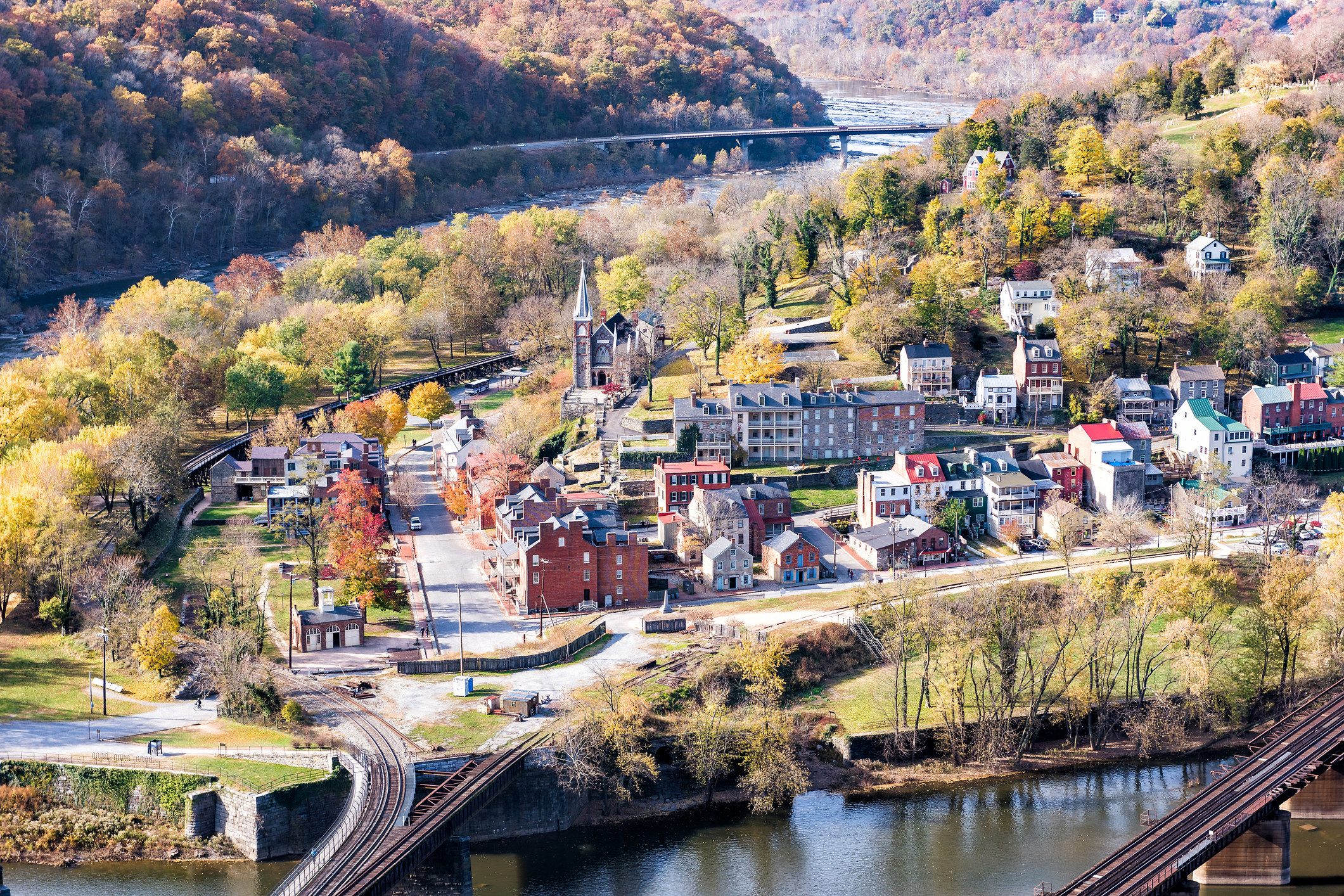 A forest filled with colorful, fall foliage surrounds a small village town by a river