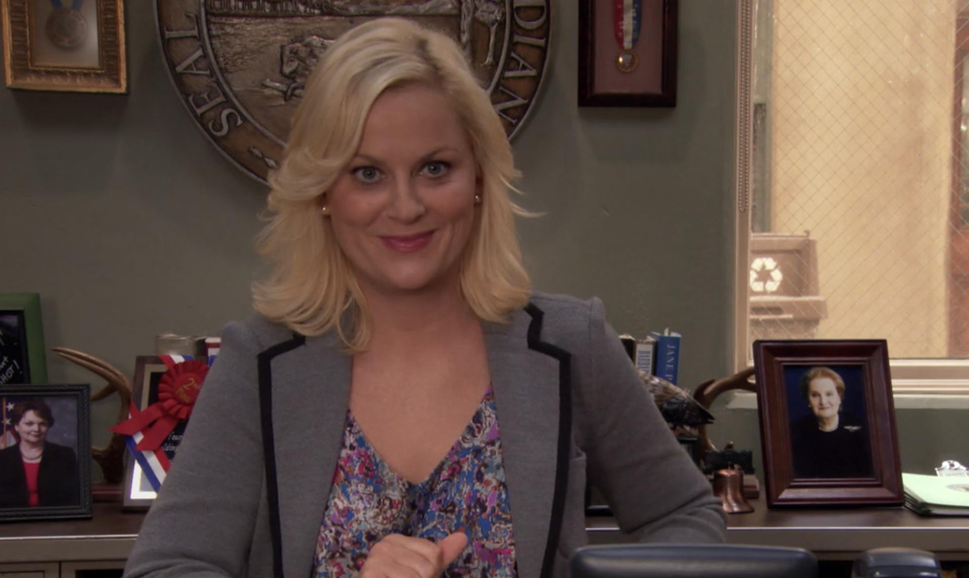 莱斯利在她的办公桌前咧着嘴笑,身后是有权势的女性政治家的照片