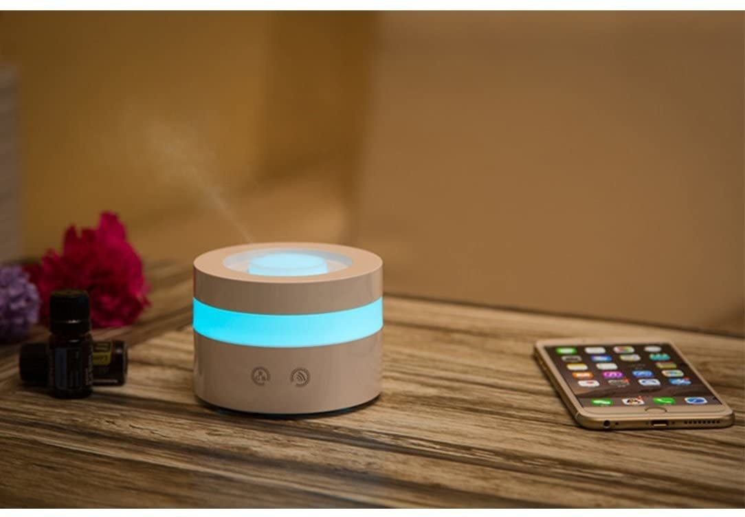 An essential oil diffuser with a blue light giving off mist