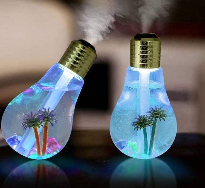 Two llghtbulb shaped humidifiers giving off steam with little palm trees in them