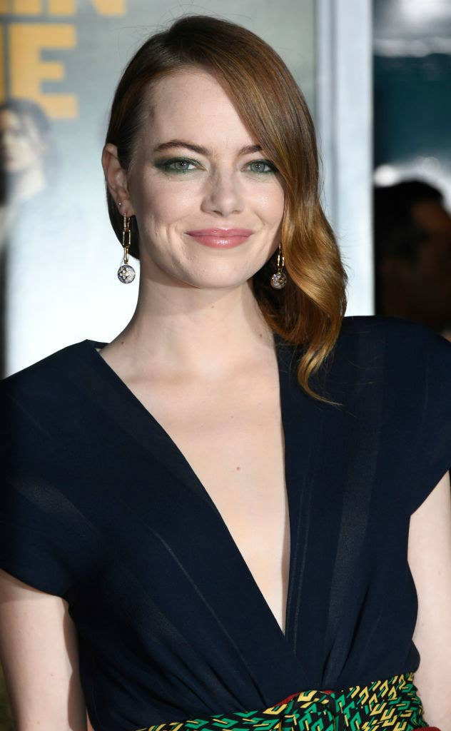 Emma Stone smiling at a camera on the red capret