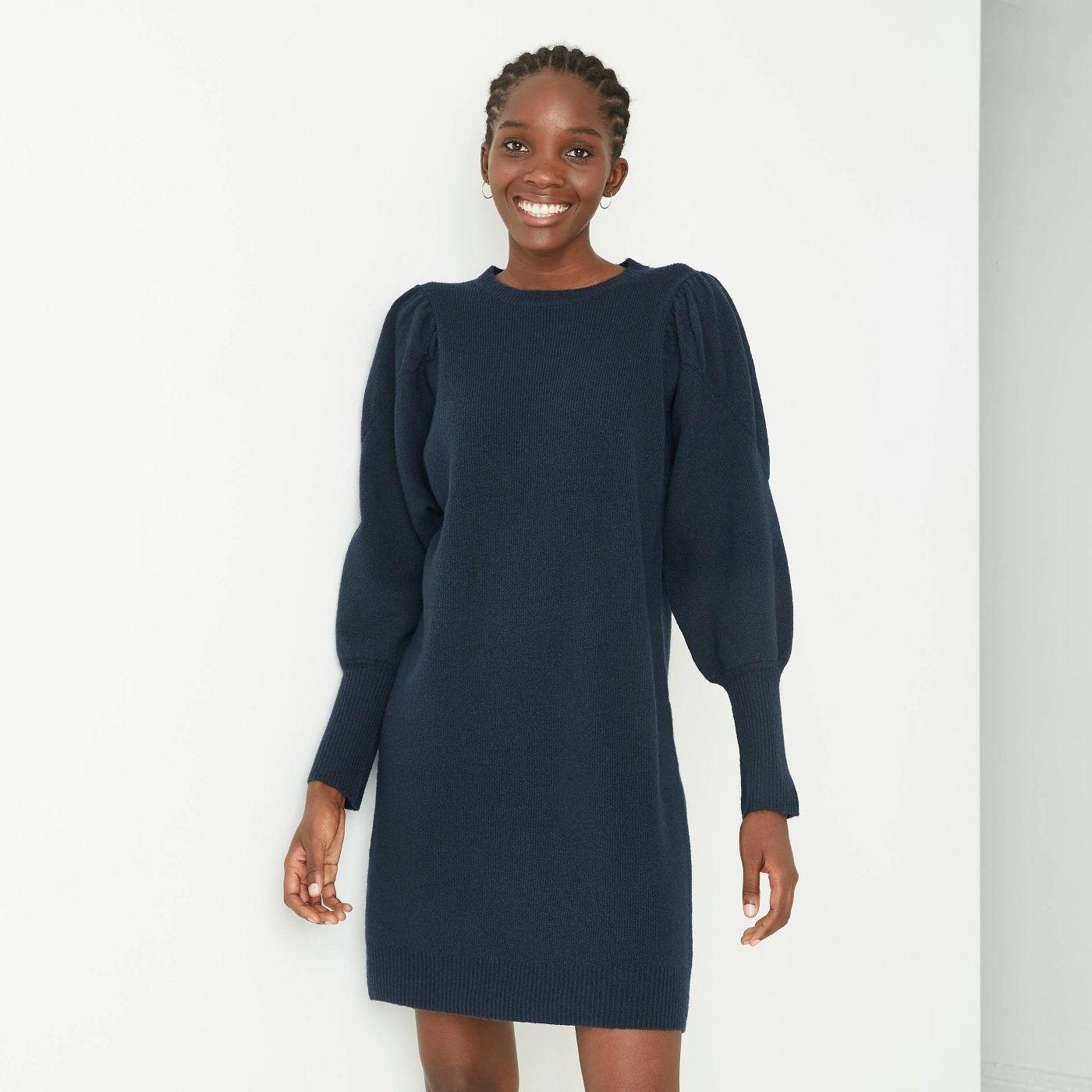 Model wearing the navy sweater dress
