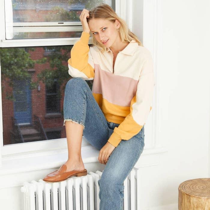 Model wearing the yellow cream sweatshirt