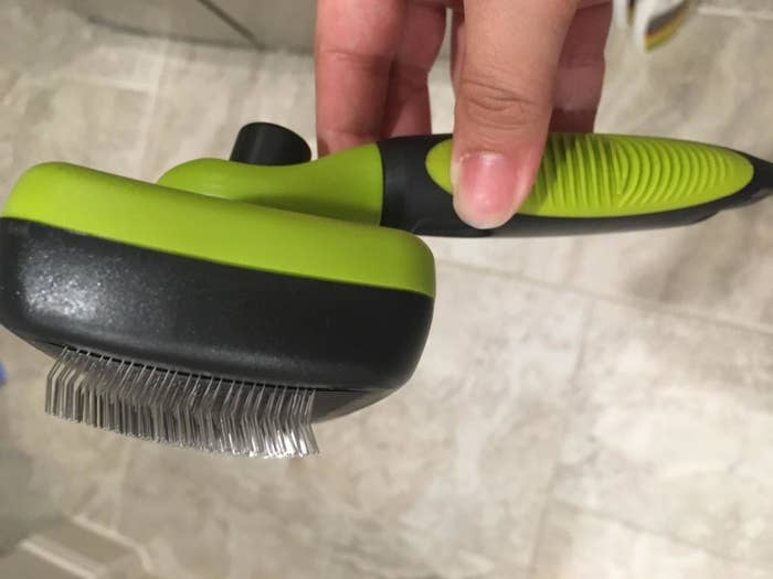 The brush, with metal bristles fully extended and long handle with grips