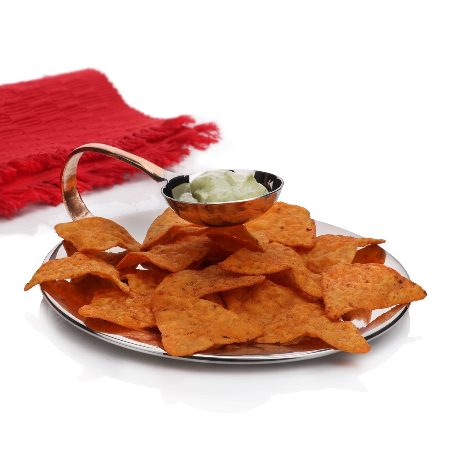 A plate full of nacho chips, with dip hanging above it in the small bowl.