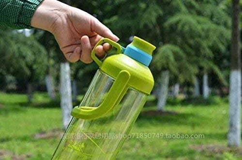 Person holding a green water bottle outdoors.