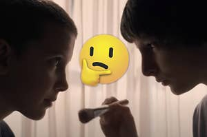 Mike is putting makeup on Eleven's face with a think face emoji in the center