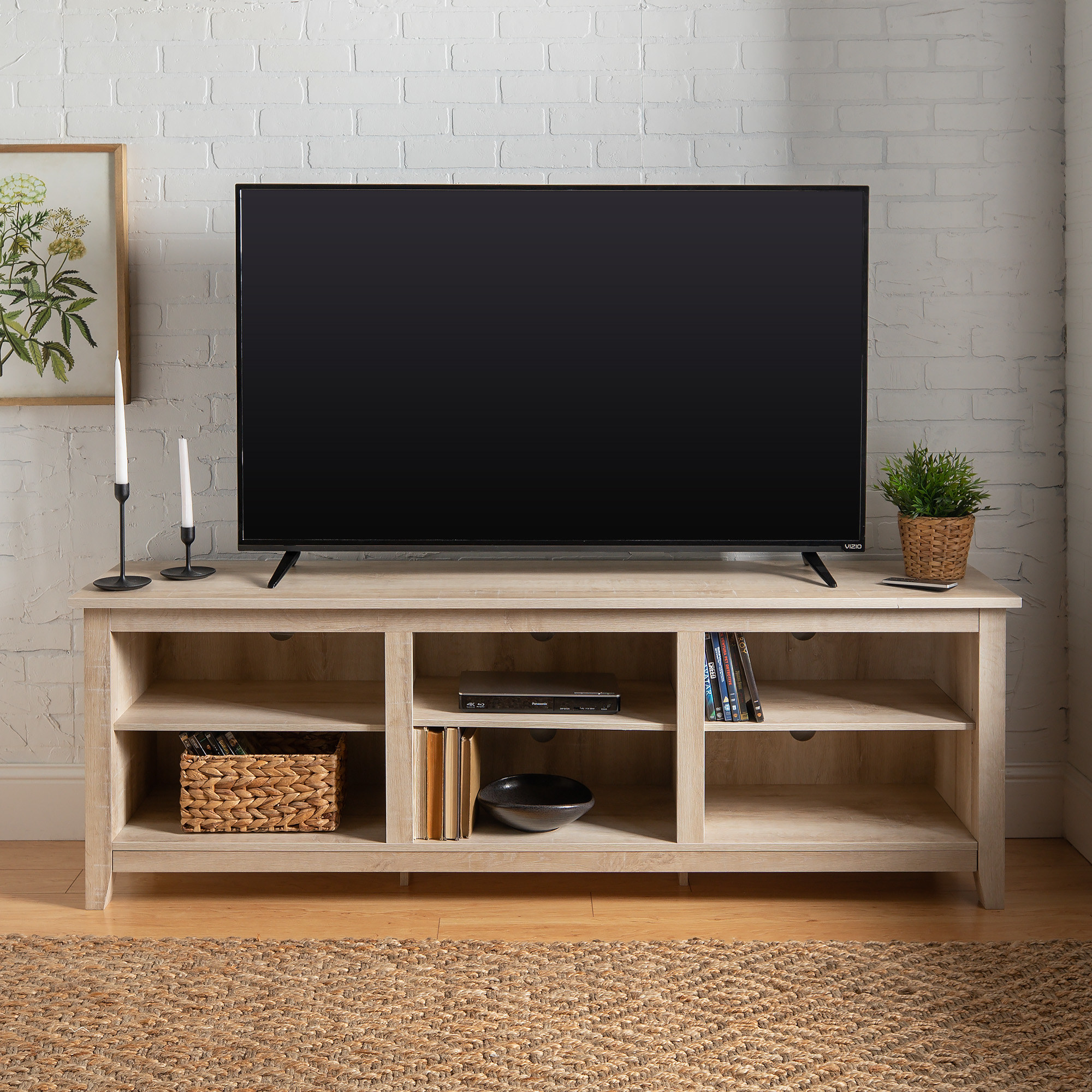The tan TV stand with storage shelves and a TV on top