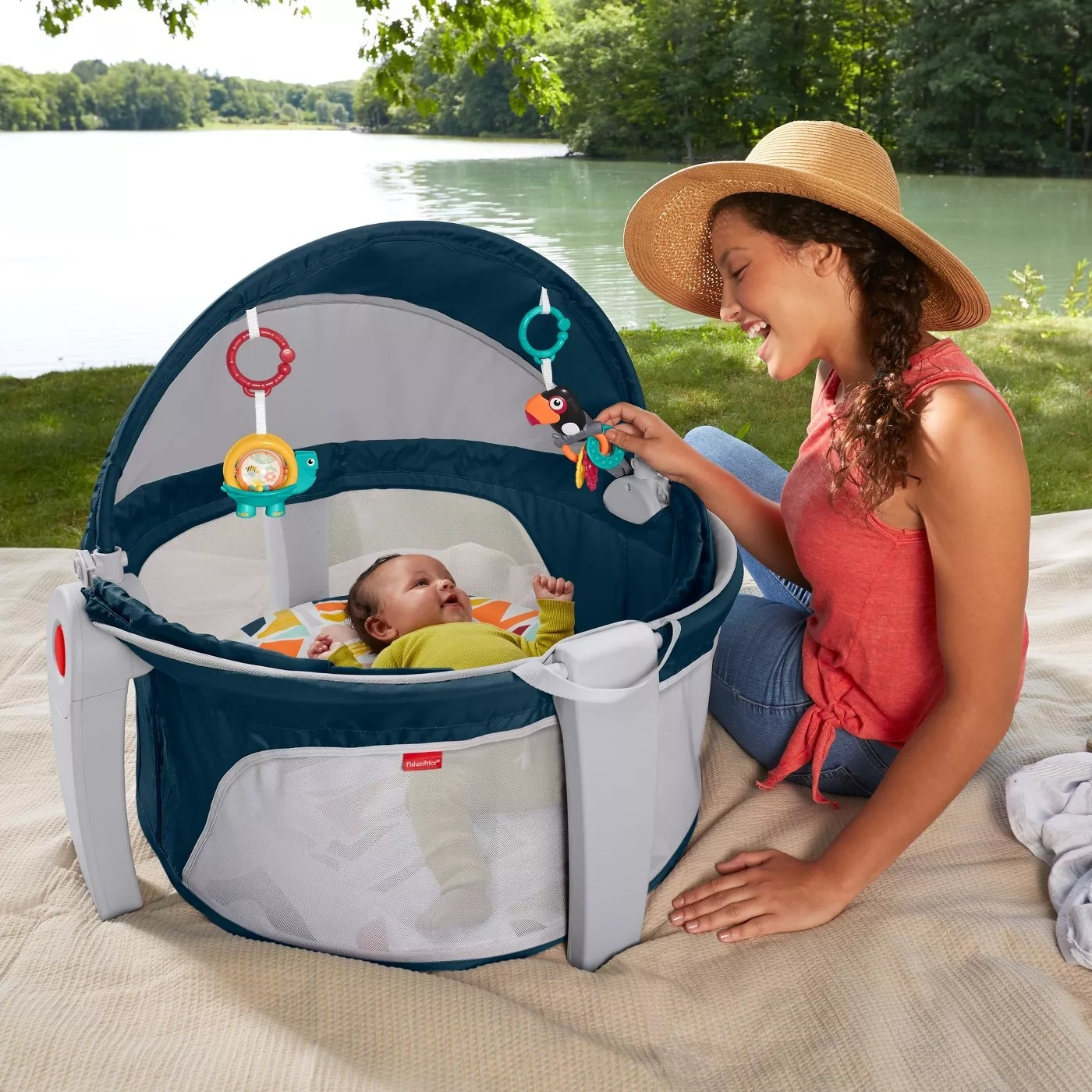 2-in-1 portable infant play space and napping spot with a canopy and two removable toys