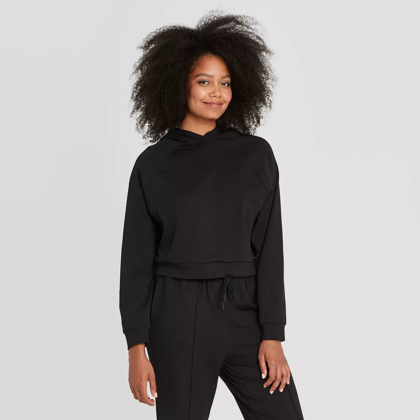 A model wearing a black, hooded sweater with a drawstring detail