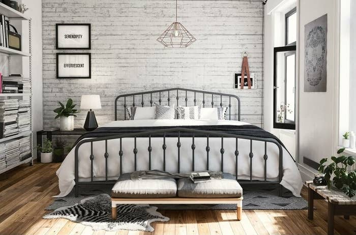 A gray metal bed frame with a full size mattress and white sheets