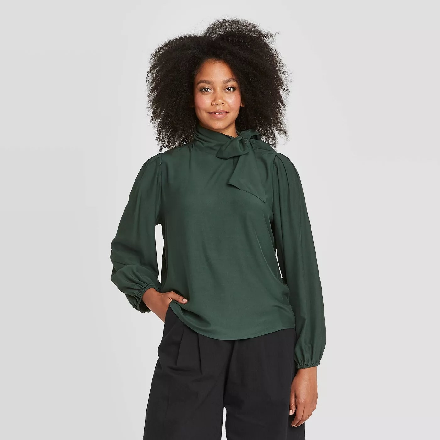 The green, high-necked, long-sleeve blouse