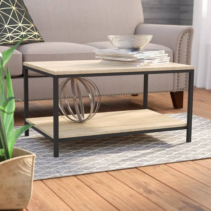 A coffee table with metal frame and light wooden top and lower shelf
