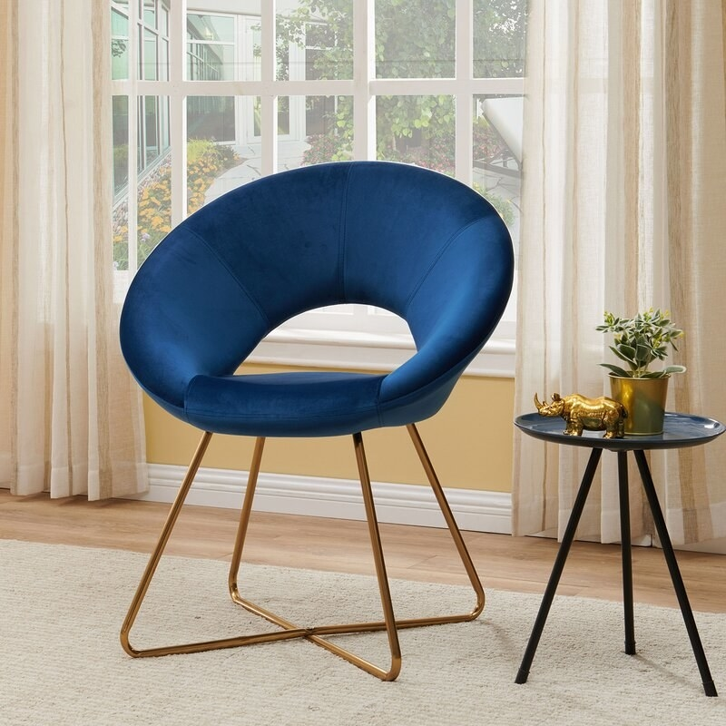 A blue velvet round chair with gold metal legs