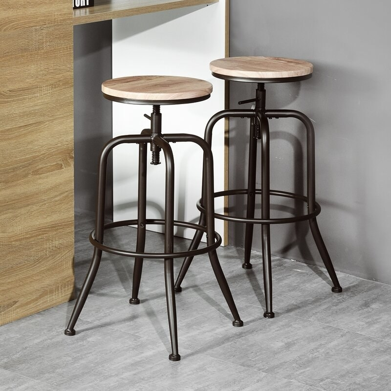 Two bar stools with metal legs and round wooden tops with adjustable heights