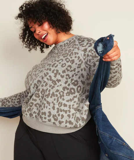 A person wears a leopard print sweater with a denim jacket around their waist