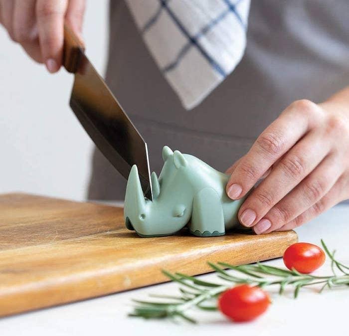 A knife is sharpened using the rhino-shaped blade sharpener