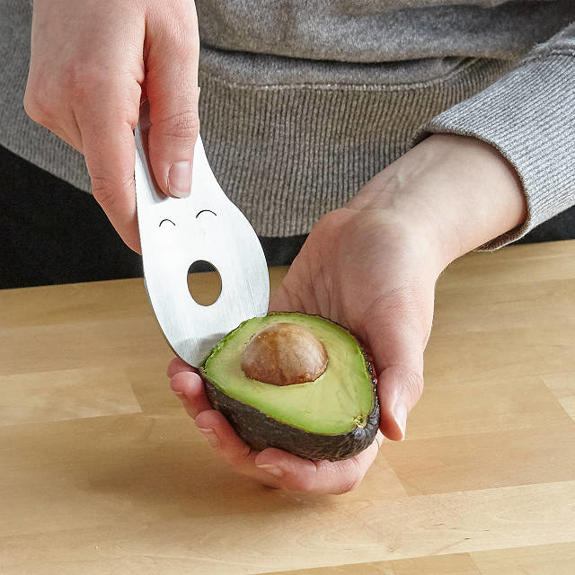 The avocado multi-tool, which resembles an avocado with a smiling face, is used to scoop out an avocado