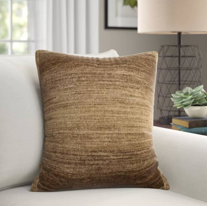 The throw pillow in neutral/brown on a white couch