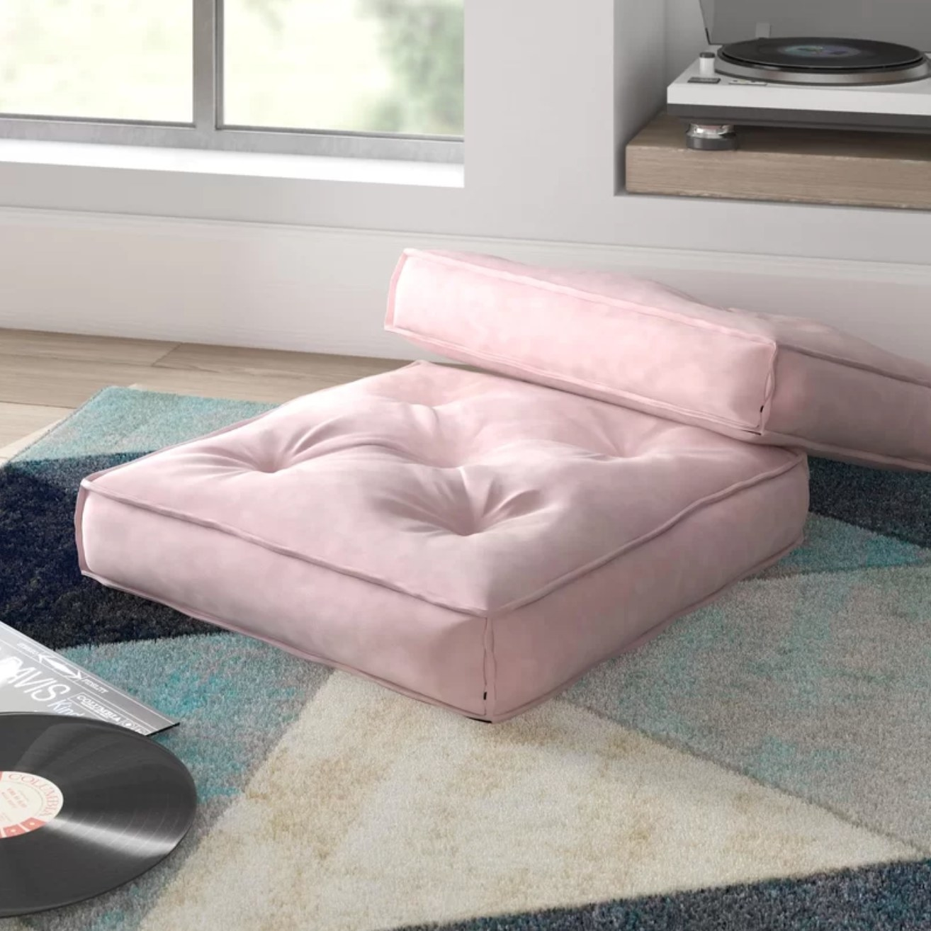 The pink floor pillow on a colorful rug