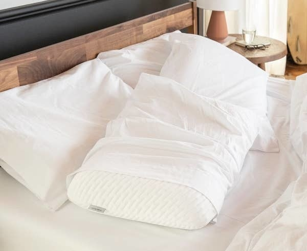 The white pillow with a white pillowcase over it