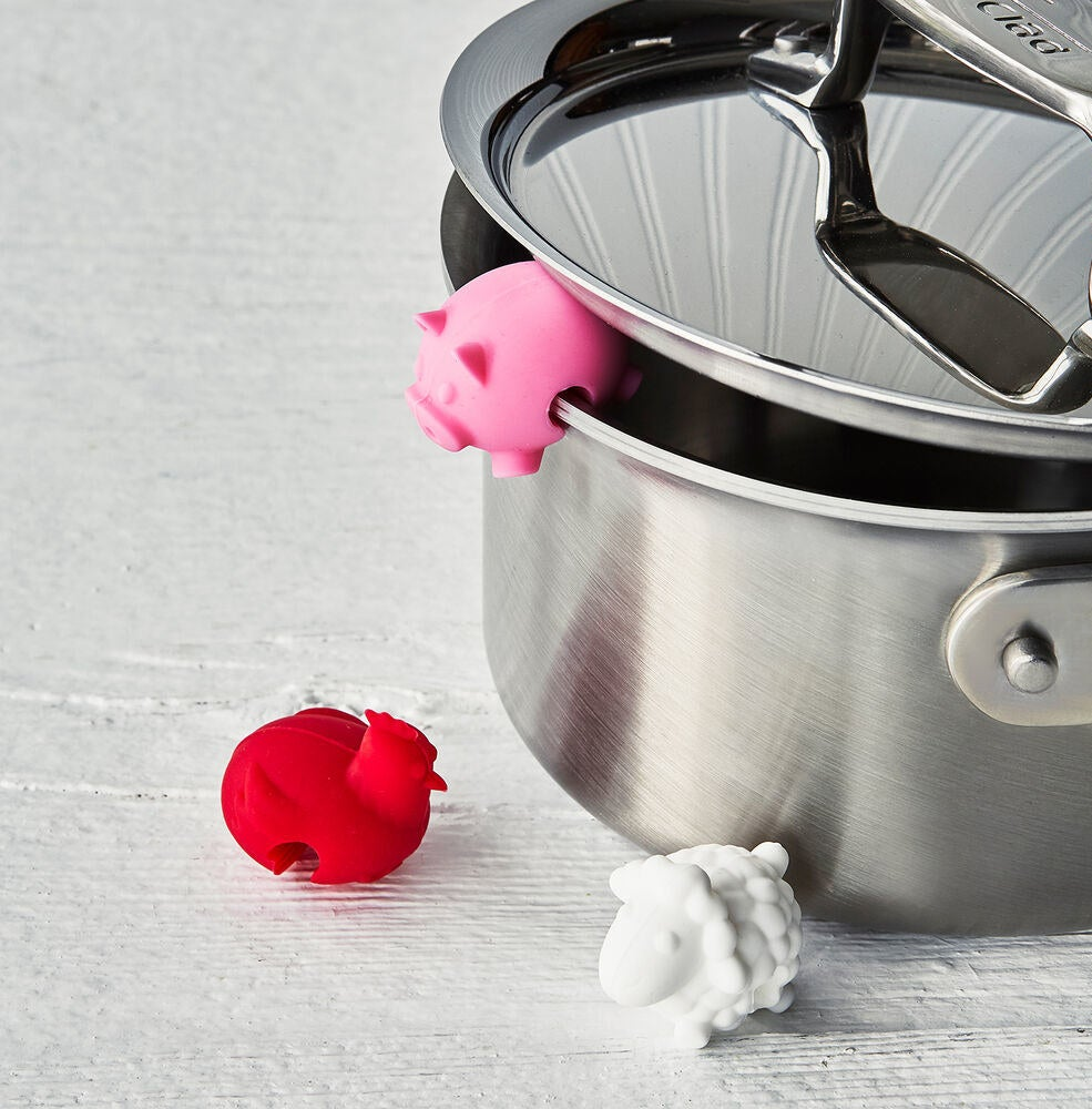 A pig, rooster, and sheep pig rests which fit perfectly on the pot to prop up the lid