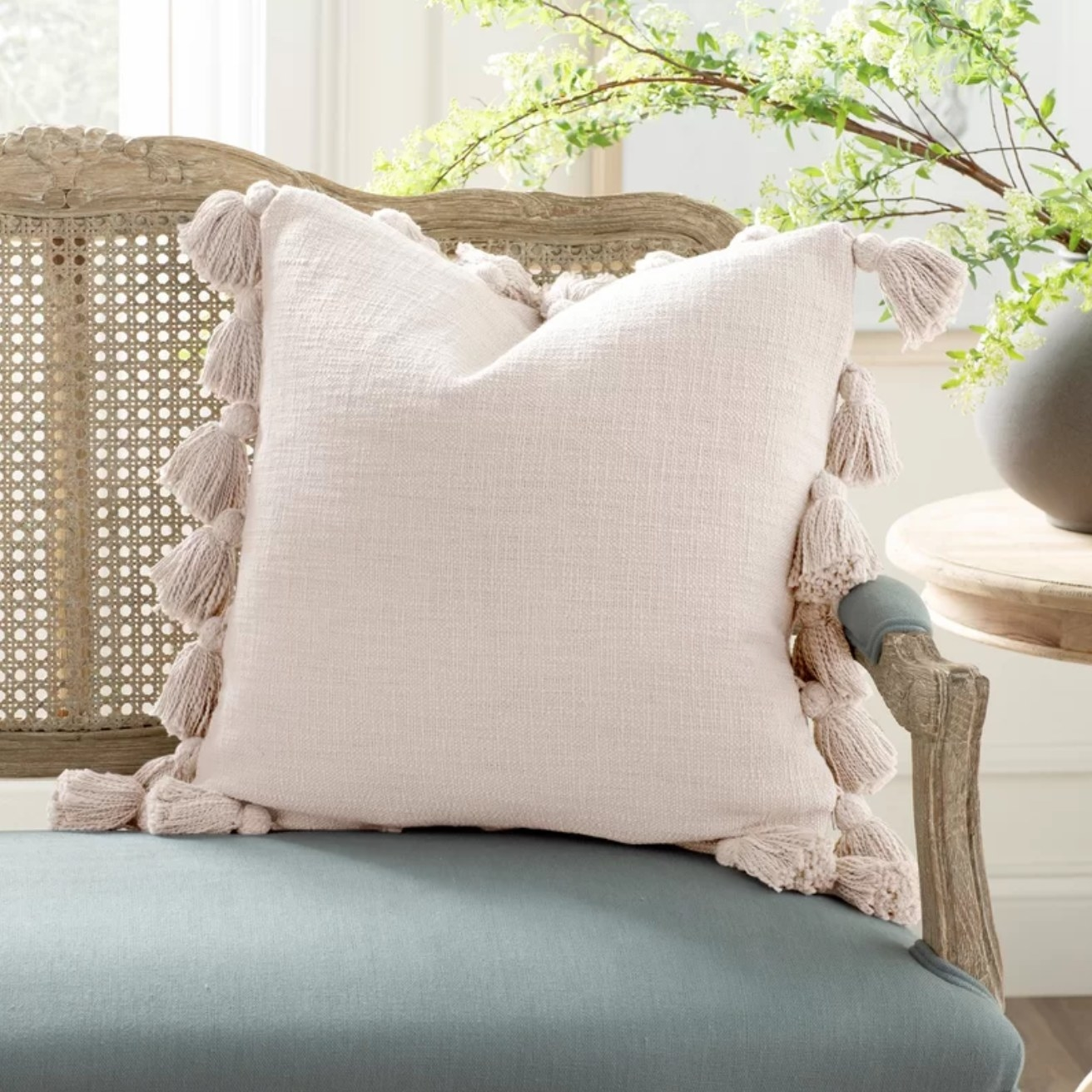 The pink decorative throw pillow on a cane bench