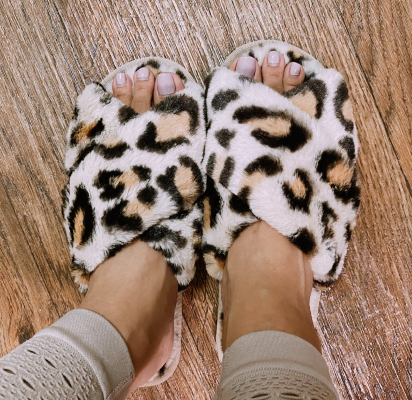Reviewer wearing the faux-fur, criss-cross strap slippers in white leopard print