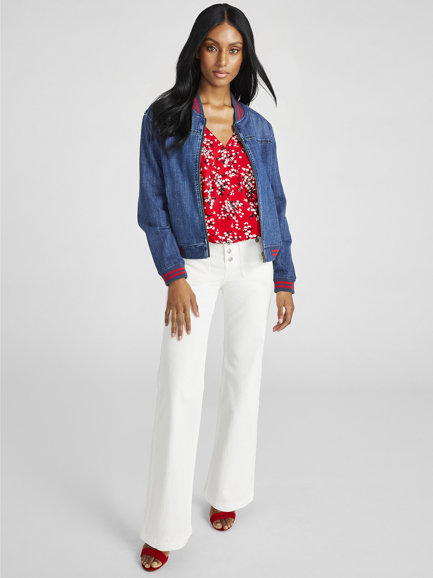 Model wears denim bomber jacket with red top, white pants and red heels