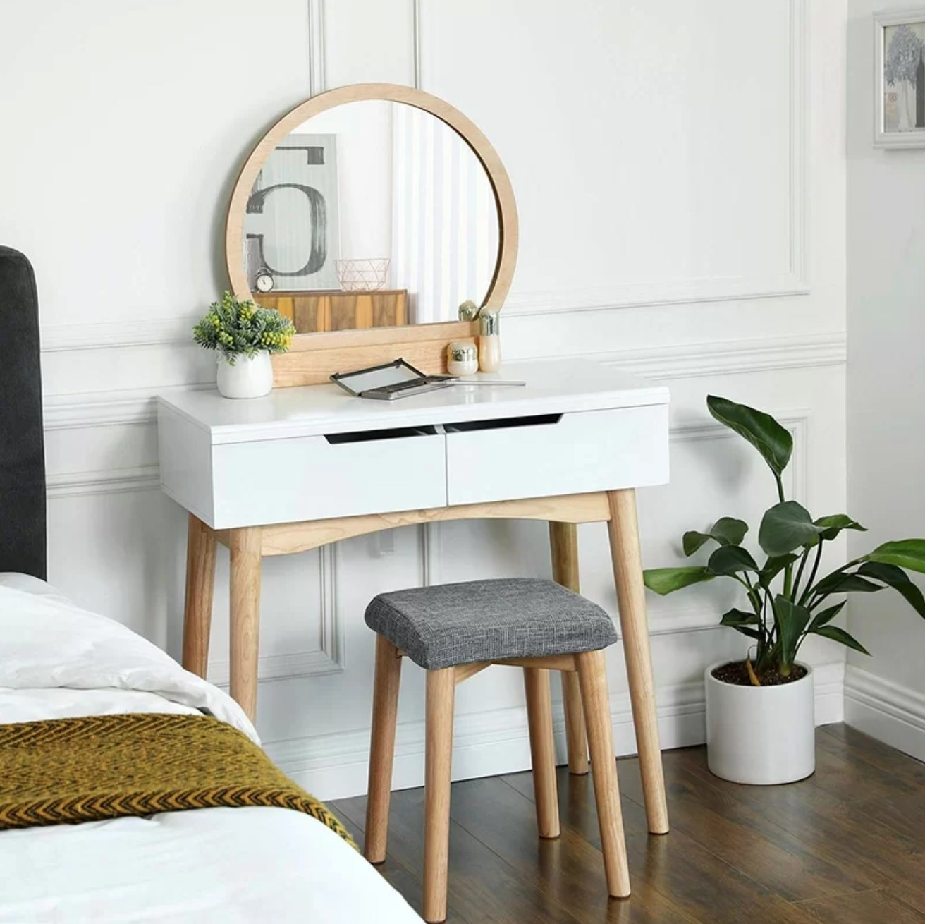 The vanity set natural/white in a bedroom next to a bed and plant