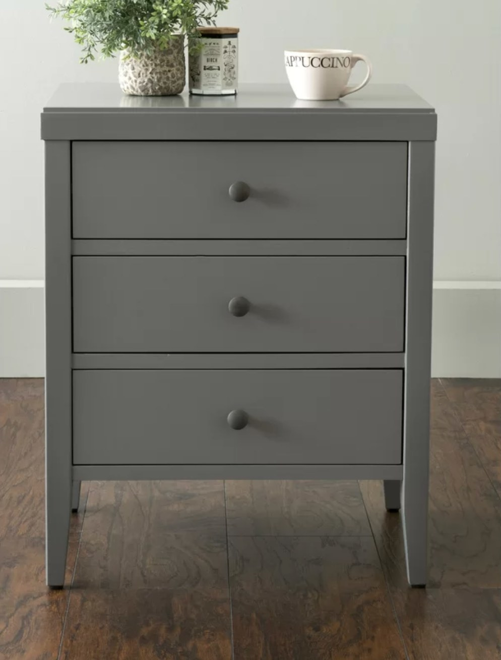 The three drawer nightstand in gray with a coffee cup and plant on top