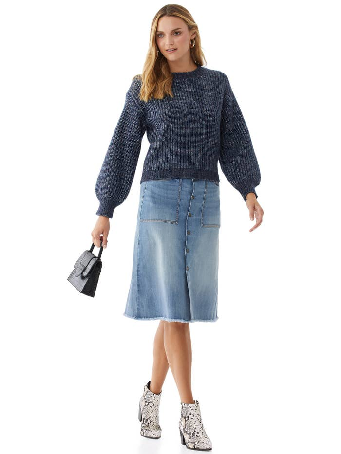 Model wears denim boot skirt with sweater and booties.