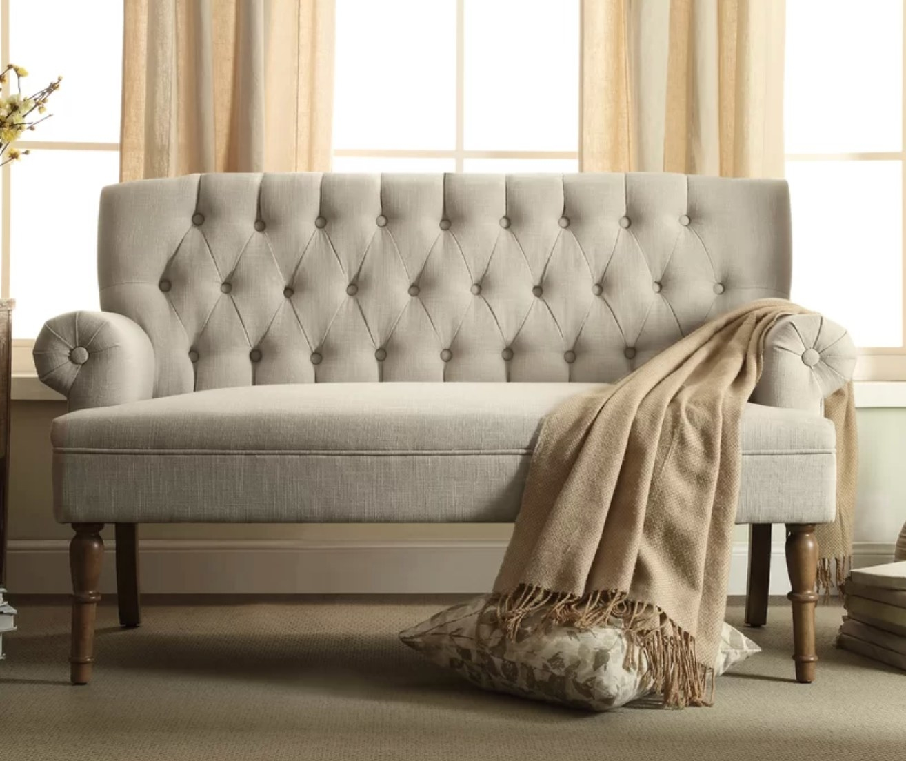 The rolled arm sofa in beige with a brown blanket draped over it