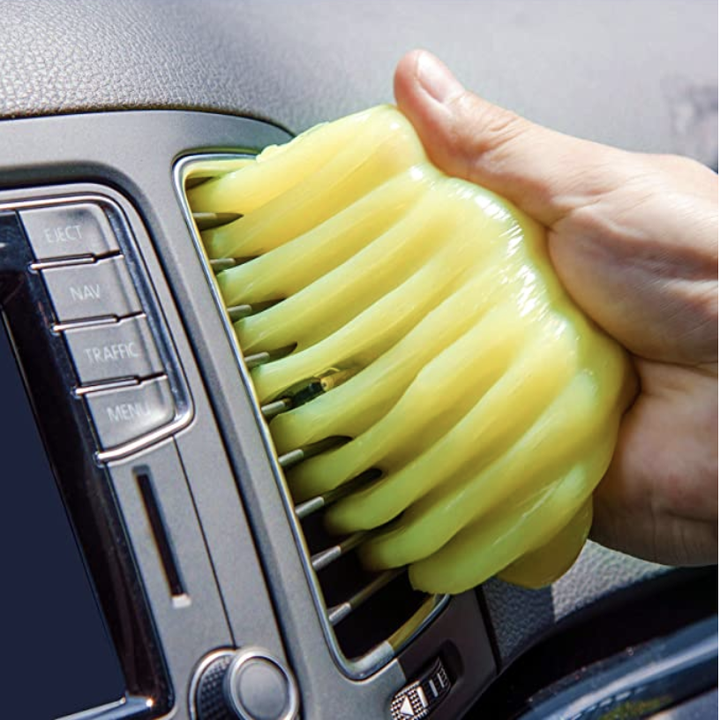 Model using yellow gel to clean an A/C unit in a car