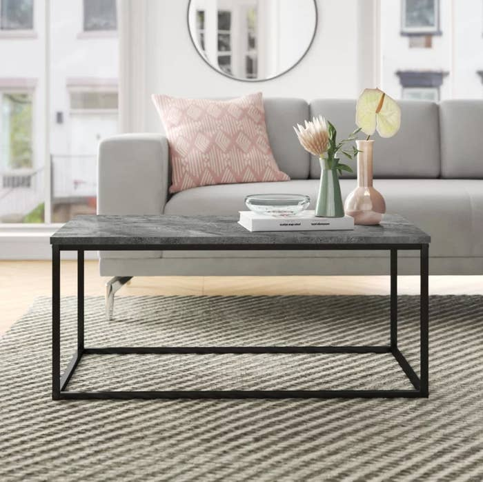 The coffee table in black in front of a gray sofa with a pink pillow