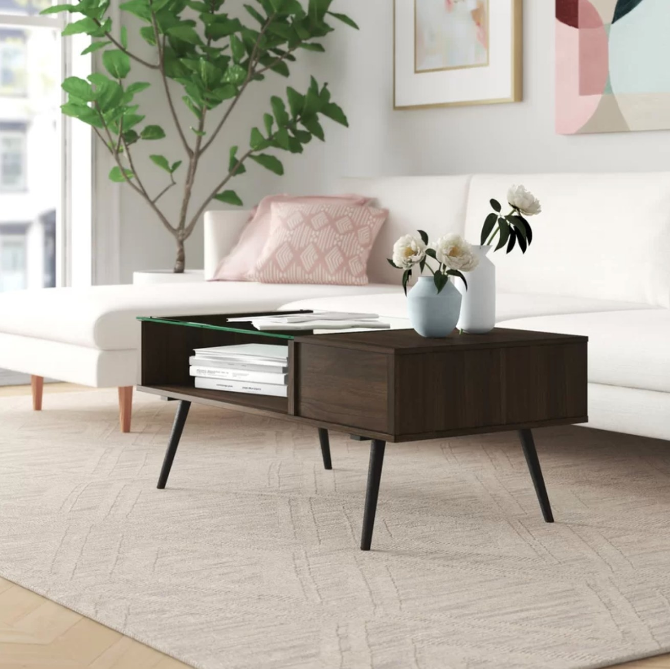 The coffee table in dark walnut holding books and a vase of flowers