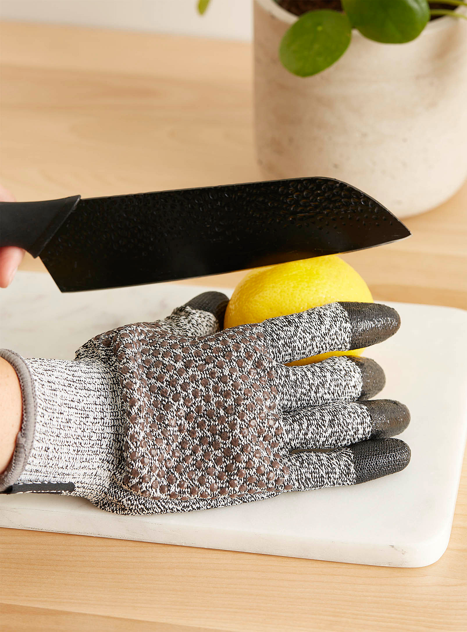 A person wearing a thick glove while cutting a lemon with a large knife