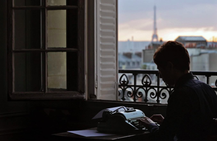 silhouette of a man typing on a typewriter with the Eiffel tower in the background