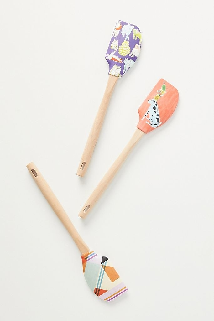 Three spatulas with different patterns: a multi-colored geometric pattern, a quirky illustrated dog, and a pattern with colorful illustrated cats