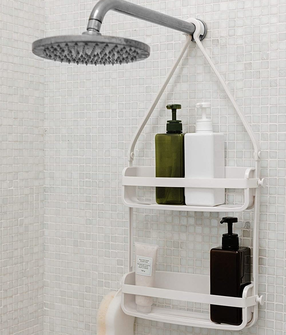 A two tiered shower caddy hanging from a shower hose