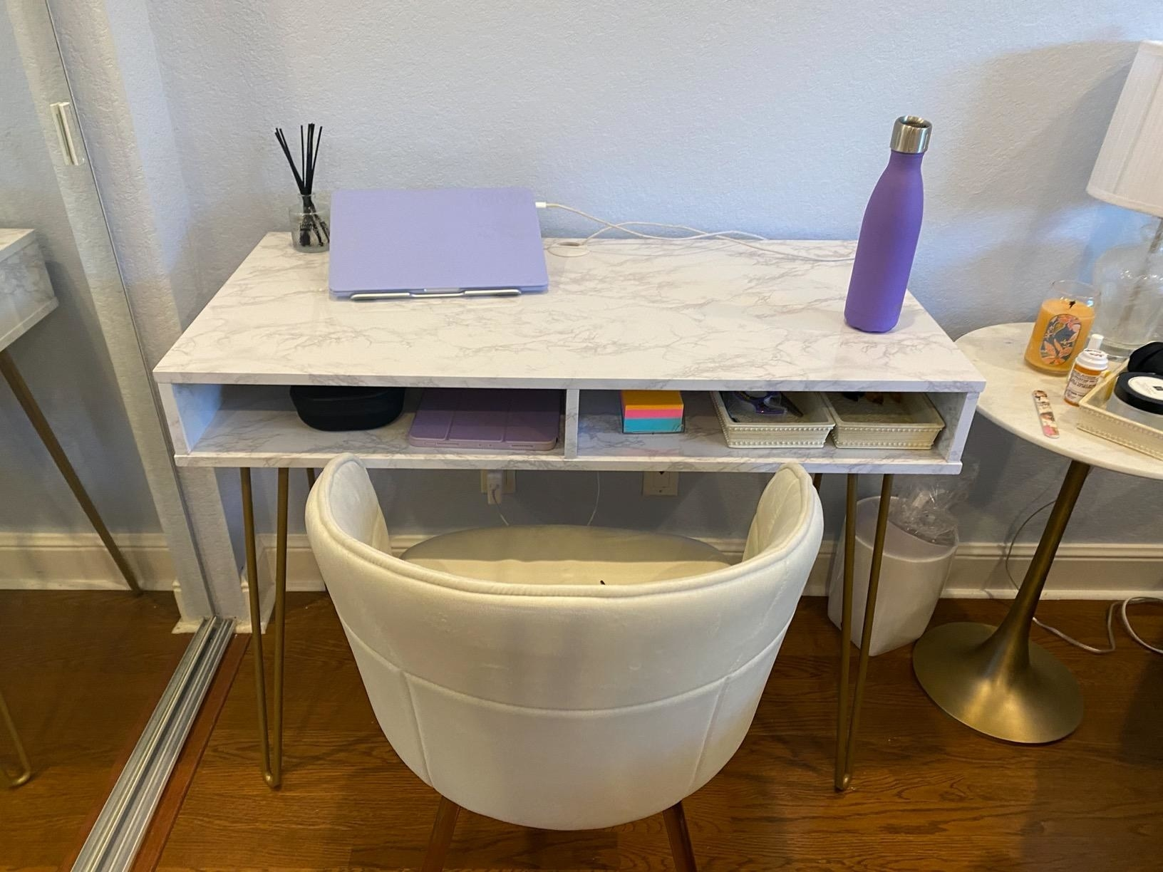 A reviewer showing the marble desk with two cubbies and metal legs
