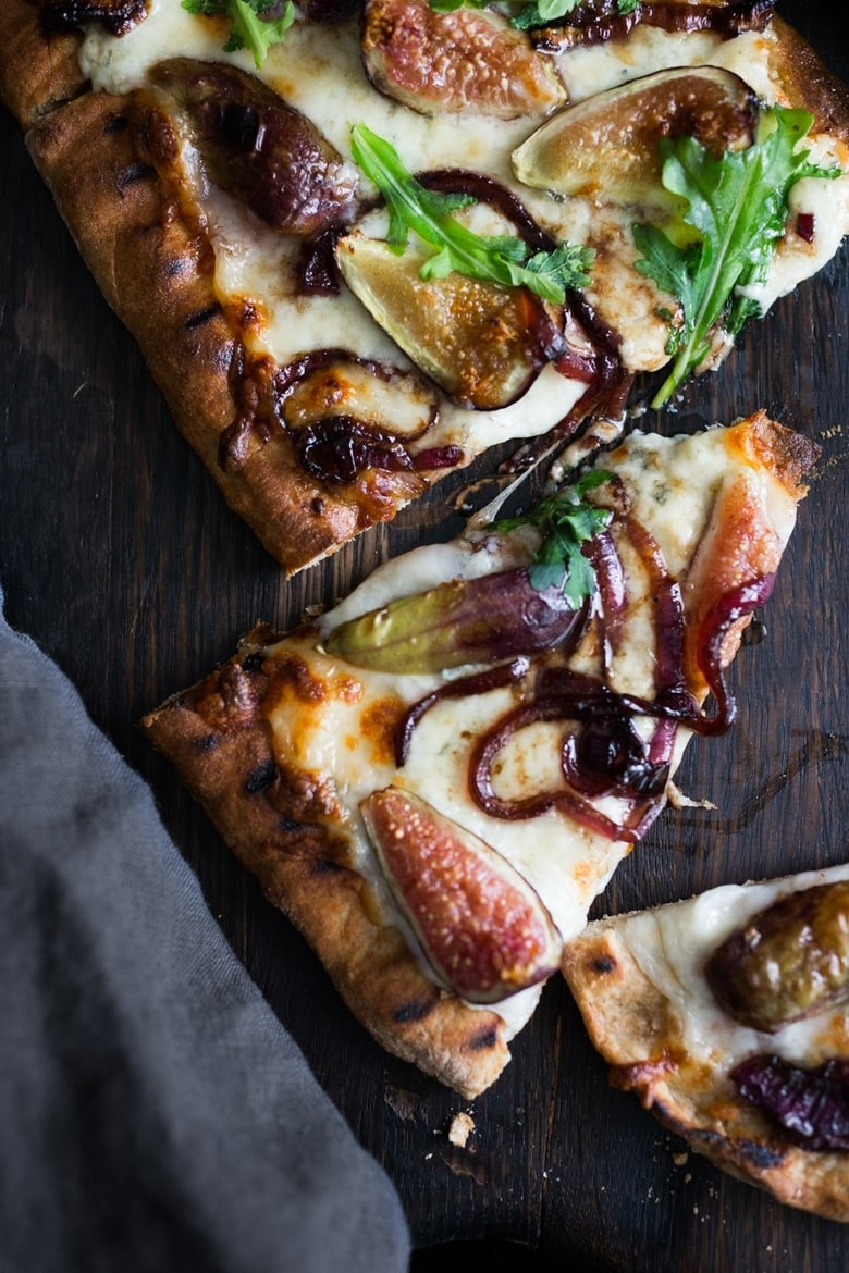 A sliced grilled pizza topped with lots of cheese, caramelized onions, and sliced figs.