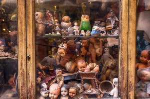 An old cabinet filled with creepy old dolls and figurines