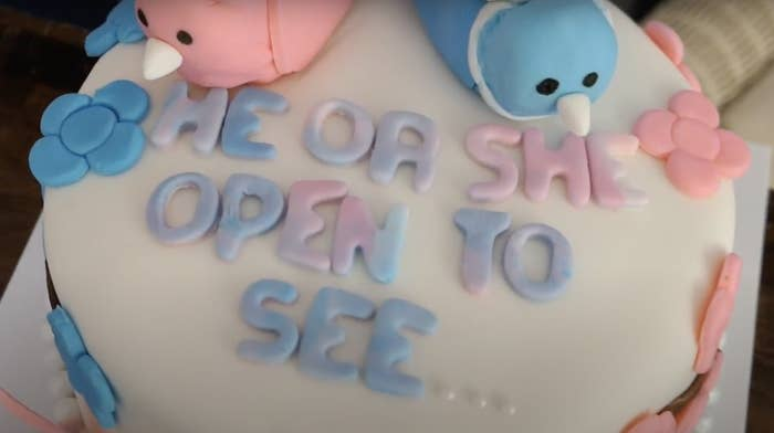 """A gender-reveal cake with the words """"He or she, open to see"""" in blue and pink icing"""
