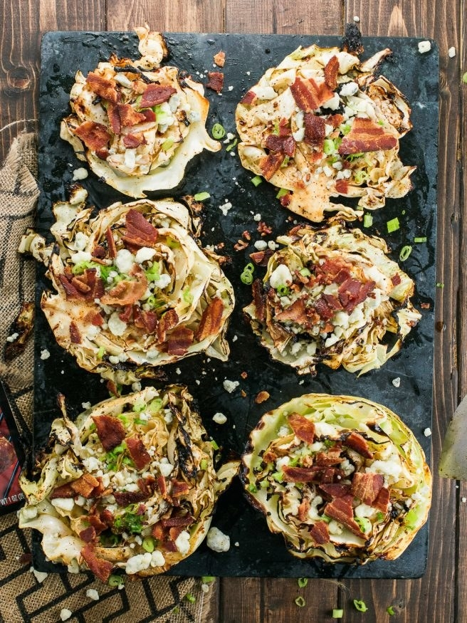 Six cabbage steak salads topped with bacon bits and blue cheese.