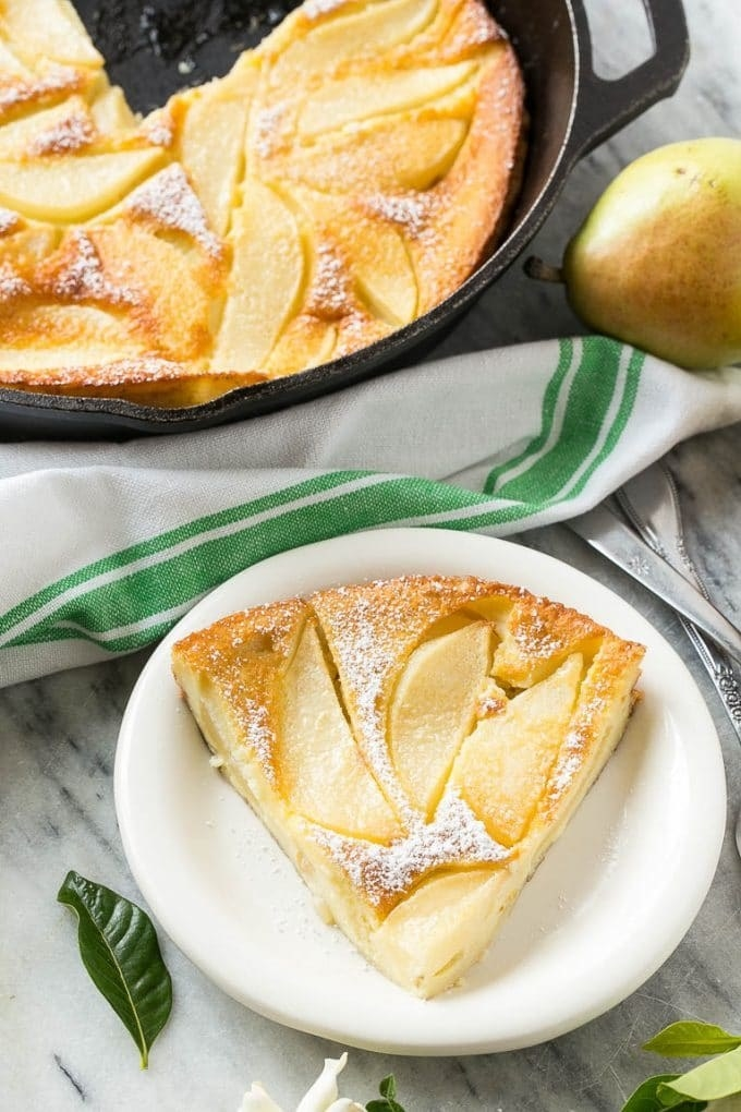 A slice of pear custard pie with powdered sugar on top.
