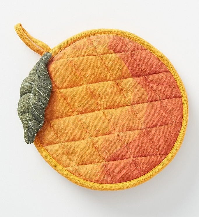 A colorful pot holder shaped like a peach