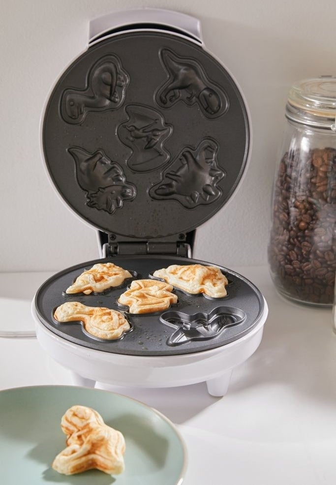 The waffle maker has a template that makes mini pancakes of various dinosaur shapes