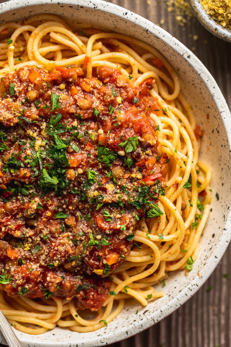 A bowl of pasta topped with vegetarian Bolognese sauce and fresh herbs.