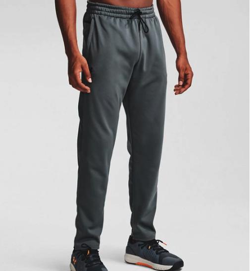 A model wearing a pair of the dark grey fleece pants